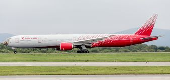 Modern passenger airplane Boeing 777-300 of Rossiya Airlines is landing in cloudy day. stock image