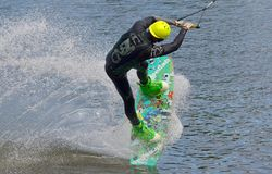 The athlete with snowboard hold on to the rope and the boat accelerates. Russia, Volgodonsk - June 18, 2015: Water snowboard. The athlete with snowboard hold on Royalty Free Stock Photography