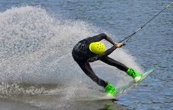 The athlete with snowboard hold on to the rope and the boat accelerates. Russia, Volgodonsk - June 18, 2015: Water snowboard. The athlete with snowboard hold on Royalty Free Stock Image