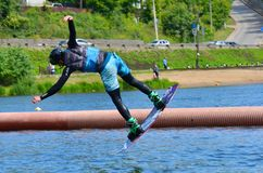 The athlete wit board hold on to the rope and the boat accelerates. Russia, Volgodonsk - June 18, 2015: Water snowboard. The athlete with snowboard hold on to Stock Images