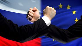 Russia vs EU confrontation, countries disagreement, fists on flag background. Stock photo royalty free stock images