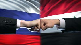 Russia vs Syria conflict, international relations, fists on flag background stock footage