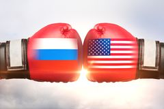 Russia vs USA concept. Red boxing gloves with country flags against each other on cloudy sky background. Russia vs USA concept. 3D Rendering stock images