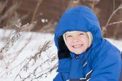 Happy boy lying in a snow stock photos