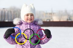 Russia, Yasny city, Orenburg region, school ice rink, 12-10. Olympic rings in the hands of a beautiful girl. A little girl holds five Olympic rings in her hands Royalty Free Stock Photos