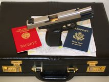 Russian agent. Handgun and two passports with suitcase and map for agent Stock Images