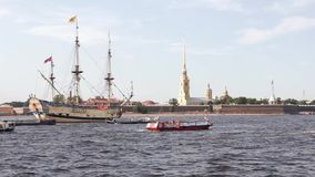 Russian ancient military combat sailing ship on a festive parade in Saint Petersburg in the Neva River and tourist boats stock video