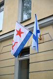 The Russian Andreevsky flag and flag of Navy of the USSR hang on a building facade Royalty Free Stock Photography