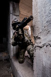 Russian army soldier shoots a machine gun out of hiding in an abandoned building. Military man in camouflage kneels in the doorway and aiming a gun. Located in a stock image