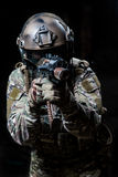 Russian army soldiers in a mask shoots a machine gun. Military man fully dressed in camouflage - gloves, helmet, goggles, headphones. It keeps automatic machine royalty free stock photo