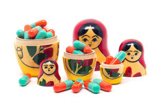 Russian Babushka nesting dolls and orange green capsules Royalty Free Stock Photos