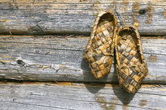 Russian bast shoes and wooden wall Royalty Free Stock Image