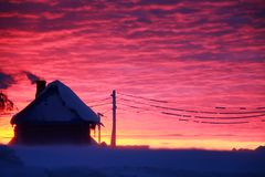 Crimson heaven. The Russian bath against the background of a crimson sunset. Winter, Russia Stock Images