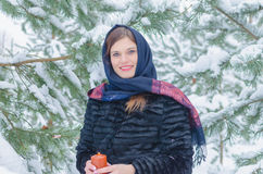 Russian beautiful girl near the Christmas tree in the woods, lit by candles. Royalty Free Stock Photos