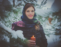 Russian beautiful girl near the Christmas tree in the woods, lit by candles. Royalty Free Stock Photography