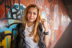 Russian beautiful smiling teenager girl with long blond hair and make up near the wall  graffiti, selective focus. Russian beautiful smiling teenager girl with Stock Photography