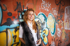 Russian beautiful smiling teenager girl with long blond hair and make up near the wall  graffiti, selective focus. Russian beautiful smiling teenager girl with Royalty Free Stock Photo