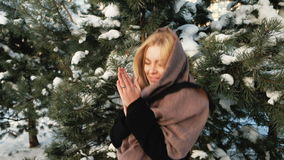 Russian beautiful woman jumping in pine forest outdoors. Attractive blond female in black coat, brown scarf tissue on head, jumps, skips, warming hands stock footage