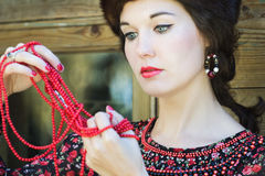 Russian beauty is looking on red coral beads in royalty free stock image