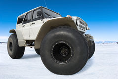 Russian bigfoot againsr blue sky. Off road vehicle at winter frozen Baikal stock photos