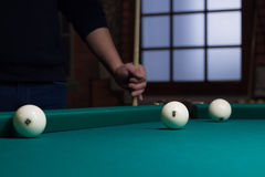 Russian billiard balls on green game table cloth and player. Close-up of Russian billiards game in process: three white balls on green game table cloth and Stock Photos