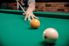 Russian billiards, man plays and beats cue on white ball.  stock photo