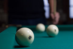 Russian billiards white balls on green table and player. Close-up of Russian billiards game in process: three white balls on green game table cloth and player Royalty Free Stock Photography