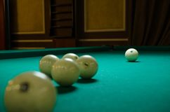 Russian billiards white balls, yellow cue ball, wooden cue on a large table with green cloth. Russian billiards white balls, yellow cue ball on a large table Stock Image