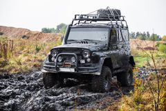 Russian black off road car UAZ in mud Stock Photos
