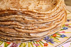 Russian blini. Stack of pancakes on a variegated dish, traditional Russian specialities, take close-up Royalty Free Stock Photography