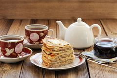 Russian bliny with currant jam, tea cups, pot on wooden backgrou Royalty Free Stock Images