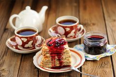 Russian bliny with currant jam, tea cups, pot on wooden background stock image