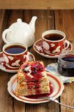 Russian bliny with currant jam, tea cups, pot on wooden backgrou Royalty Free Stock Photography