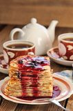 Russian bliny with currant jam, tea cups, pot on wooden background stock images
