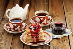Russian bliny with currant jam, tea cups, pot on wooden backgrou Stock Photo