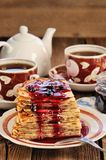Russian bliny with currant jam, tea cups, pot on wooden background stock photography
