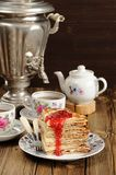 Russian bliny with raspberry jam, vintage samovar and teaware Royalty Free Stock Photo