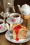 Russian bliny with raspberry jam, vintage samovar and teaware Royalty Free Stock Image