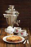 Russian bliny with vintage samovar and teaware stock photo