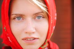 Russian blonde with blue eyes in a red kerchief is working on the farm. The concept of female beauty and perfection. A russian blonde with blue eyes in a red Royalty Free Stock Photo