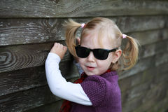 Russian blonde little girl in sunglases and red scarf against wooden wall Stock Photos