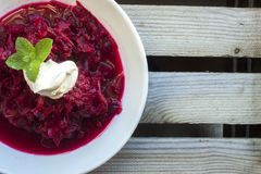 Russian borch soup. In a white soup plate, on a wooden table Royalty Free Stock Photography