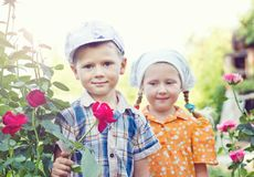 Russian boy and girl at roses. In garden Stock Photography