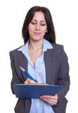 Russian businesswoman making notes on clipboard stock photos