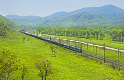 Russian cargo train against the hills landscape Royalty Free Stock Images