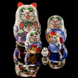 Russian Cat Nesting Doll. Set of Russian nesting dolls babushkas or matryoshkas in shapes of cat family on black mirror Stock Photography