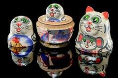 Russian Cat Nesting Doll. Set of Russian nesting dolls babushkas or matryoshkas in shapes of cat family on black mirror Royalty Free Stock Photo