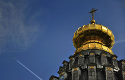 Russian Cathedral Dome, Jet Travel. A jet flies high over the shimmering golden domes of a Moscow cathedral Royalty Free Stock Image