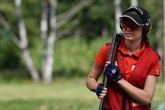 Russian championships in trap shooting. St. Petersburg, Russia - August 4, 2015: Unidentified female athlete with shotgun during the Russian championships in Stock Photo