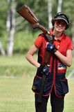 Russian championships in trap shooting. St. Petersburg, Russia - August 4, 2015: Unidentified female athlete with shotgun during the Russian championships in Stock Image